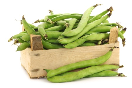 bunch of broad beans in a wooden box on a white background photo