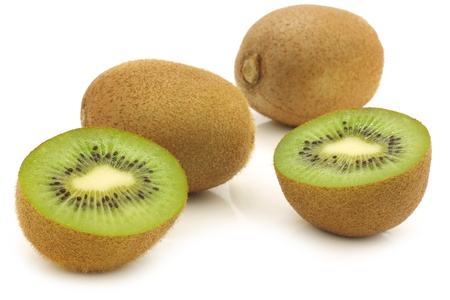 Fresh kiwi fruit and a cut one on a white background photo