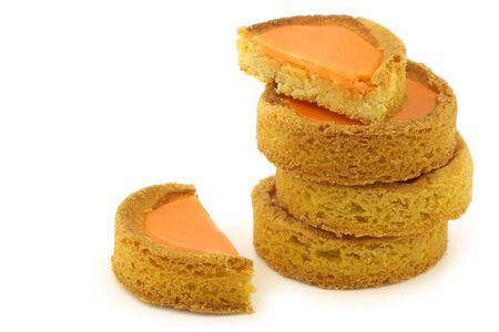 festivities: Stacked traditional Dutch orange glazed cakes sold at royal festivities on a white background