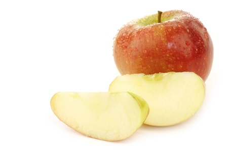 one whole braeburn apple and some pieces on a white background
