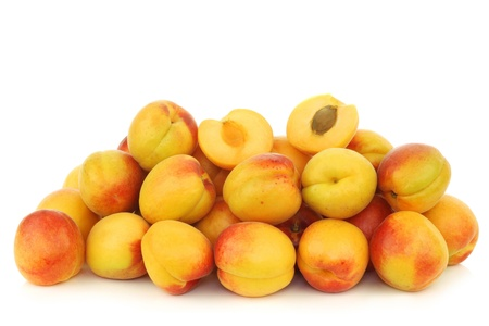 fresh colorful apricots and a cut one on a white background photo