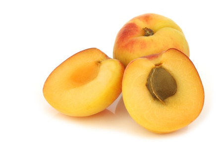 fresh colorful apricot and a cut one on a white background photo