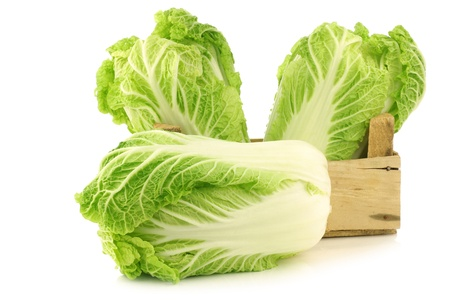 fresh chinese cabbage in a wooden crate on a white background photo