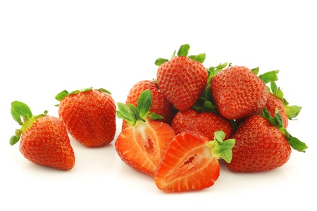 fresh strawberries and a cut one on a white background photo