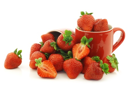 fresh strawberries and a cut one in red ceramic cups on a white background photo