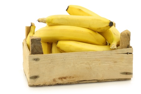 fresh bananas in a wooden crate on a white background photo