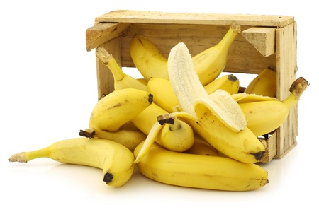 fresh bananas and a peeled one in a wooden crate on a white background Banque d'images