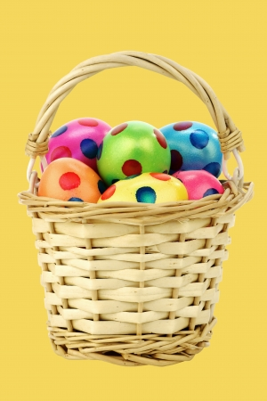 full willow: colorful easter eggs in a wicker basket on a yellow background