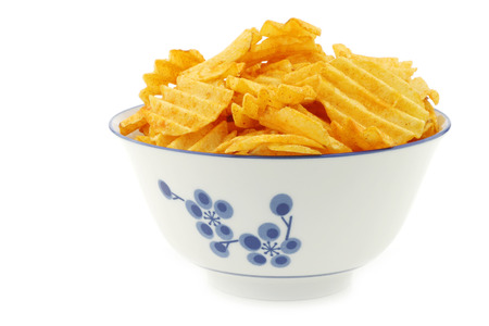 ridged: Freshly baked deep ridged potato chips in a decorated ceramic bowl on a white background