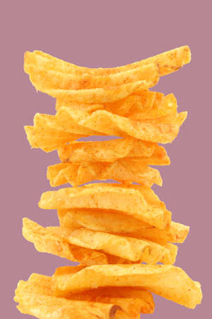 ridged: freshly baked stack of deep ridged potato chips on a purple background