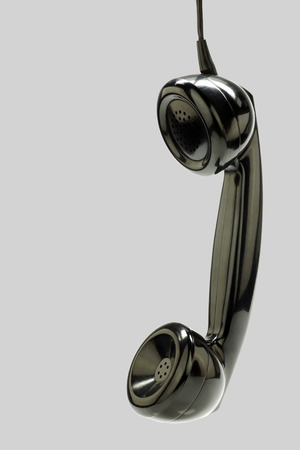 bakelite: vintage bakelite telephone horn hanging on a grey background Stock Photo