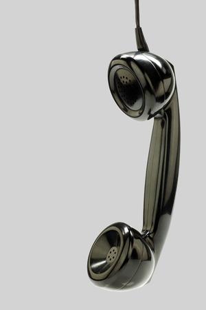 bakelite: vintage bakelite telephone horn hanging on a grey background Stock Photo