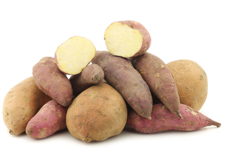 bunch of mixed sweet potatoes and a cut one on a white background