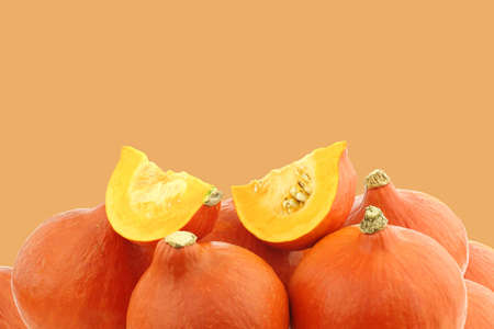 Bunch of orange pumpkins and some cut pieces on an orange background photo
