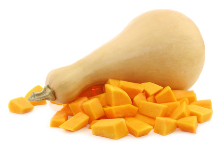 bottle shaped butternut pumpkin and some cut blocks on a white background Stock Photo