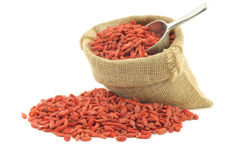 lycium: dried goji berries (Lycium Barbarum - Wolfberry) in a burlap bag with an aluminum scoop on white background