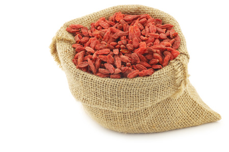 lycium: dried goji berries (Lycium Barbarum - Wolfberry) in a burlap bag on white background Stock Photo