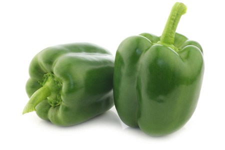 fresh green bell peppers (capsicum) on a white background