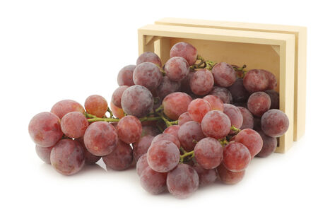 seedless: fresh red grapes on the vine in a wooden crate on a white background