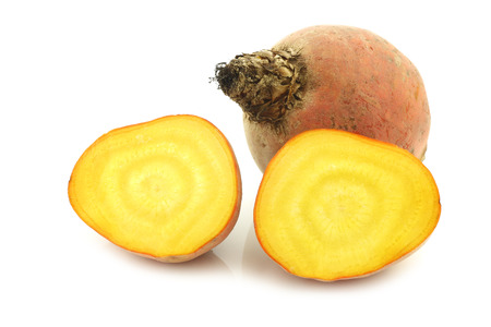 yellow agriculture: freshly harvested yellow beet and two halves on a white background