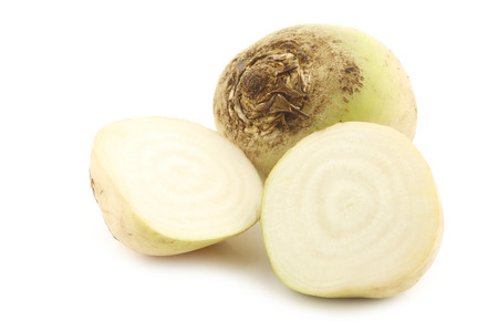 freshly harvested white beet and a cut one beets on a white background