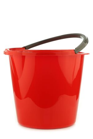 drudgery: empty red plastic household bucket with a grey handle on a white background
