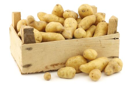 tuberosum: original french rattepotatoes (Solanum tuberosum) in a wooden crate on a white background