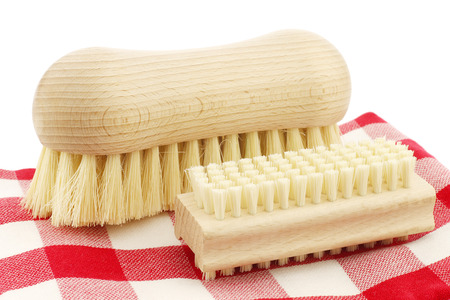 nail brush: a wooden nail brush and a wooden household brush on a red and white checkered kitchen towel on a white background Stock Photo