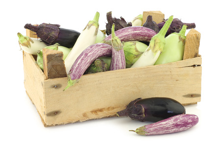 crate: fresh mixed aubergines(Cucurbita pepo), and a cut one in a wooden crate on a white background