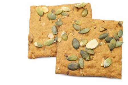 spelled: crispy spelled crackers with pumpkin seeds on a white background