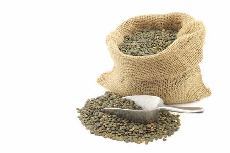 French green lentils du Puy lentilles in a burlap bag on a white background Banque d'images