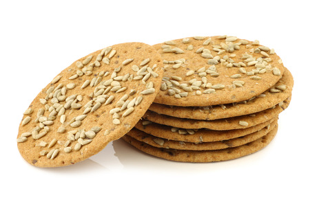 spelled: stacked crispy spelled crackers with sunflower seeds on a white background