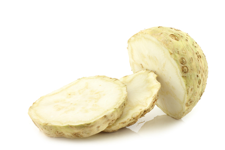 apium graveolens: fresh celery root cut into slices on a white background