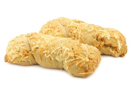 spelled: freshly baked spelled bread covered with grated cheese and a cut one on a white background Stock Photo