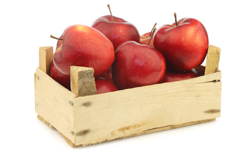 Fresh and delicious red Jonagold apples in a wooden crate on a white background Stock Photo