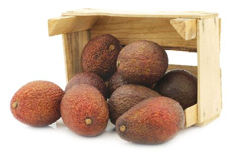 Eat ripe avocados in a wooden crate on a white background