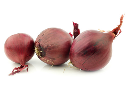 cebollas: three red onions on a white background Foto de archivo