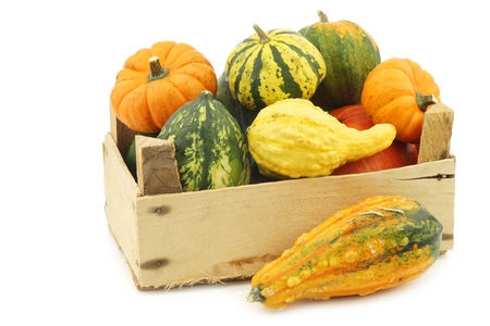 colorful decorative pumpkins in a wooden crate on a white background Stock Photo