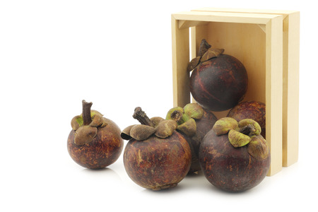 mangosteen fruits (Garcinia mangostana linn) in a wooden box on a white background Stock Photo