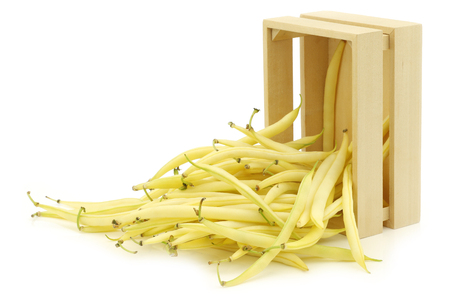 Yellow wax beans (Phaseolus vulgaris) in a wooden box on a white background