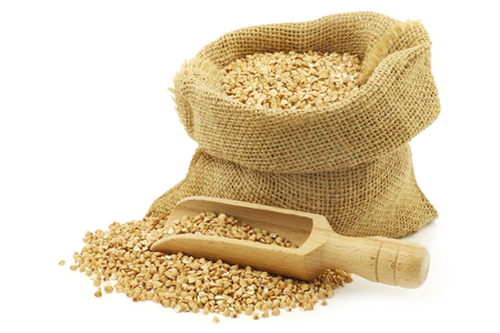 Biologically grown organic buckwheat in a burlap bag with a wooden scoop on a white background