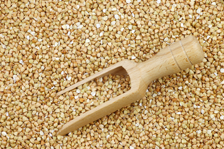 background of biologically grown organic buckwheat with a wooden scoop 版權商用圖片