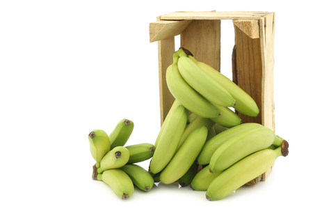small green snack bananas in a wooden crate on a white background 版權商用圖片