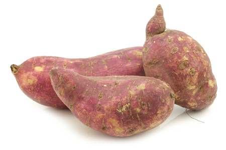 freshly harvested sweet potatoes on a white background