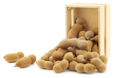 Tamarind beans in a wooden box on a white background