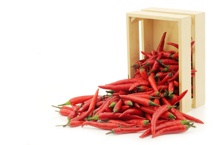 red rawit peppers (Capsicum annuum 'Bird's Eye') in a wooden box on a white background