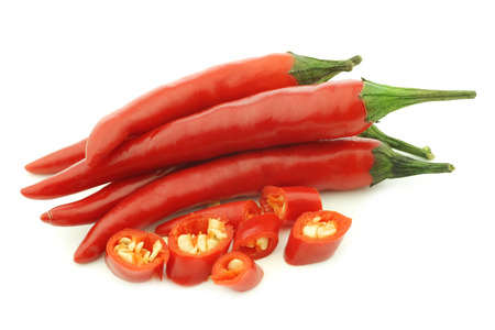 red rawit peppers (Capsicum annuum 'Bird's Eye') and a cut one on a white background 版權商用圖片