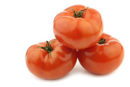 three beef tomatoes on a white background