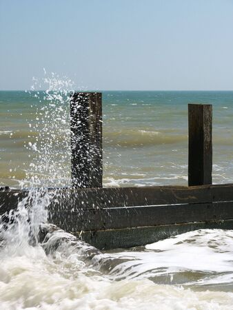 which: A seaside scene, in the foreground of which a wave is breaking on a wooden breaker, throwing spray into the air. In the background are waves, the sea and the sky. Stock Photo