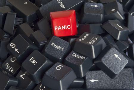 panic button: Primo piano su una pila di tasti della tastiera computer nero con pulsante rosso di panico